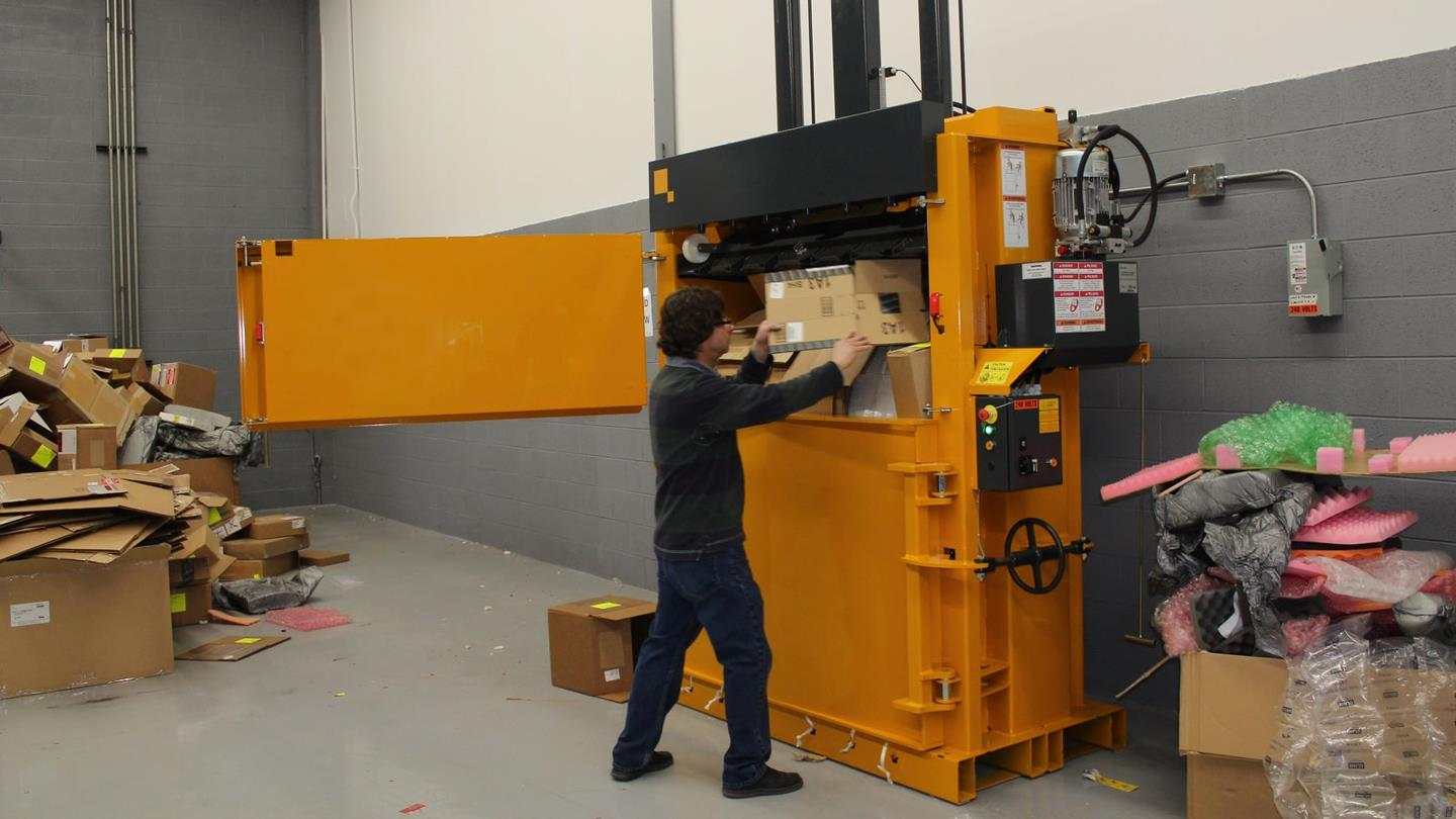 Chicago Tech employee compacts cardboard in Bramidan baler