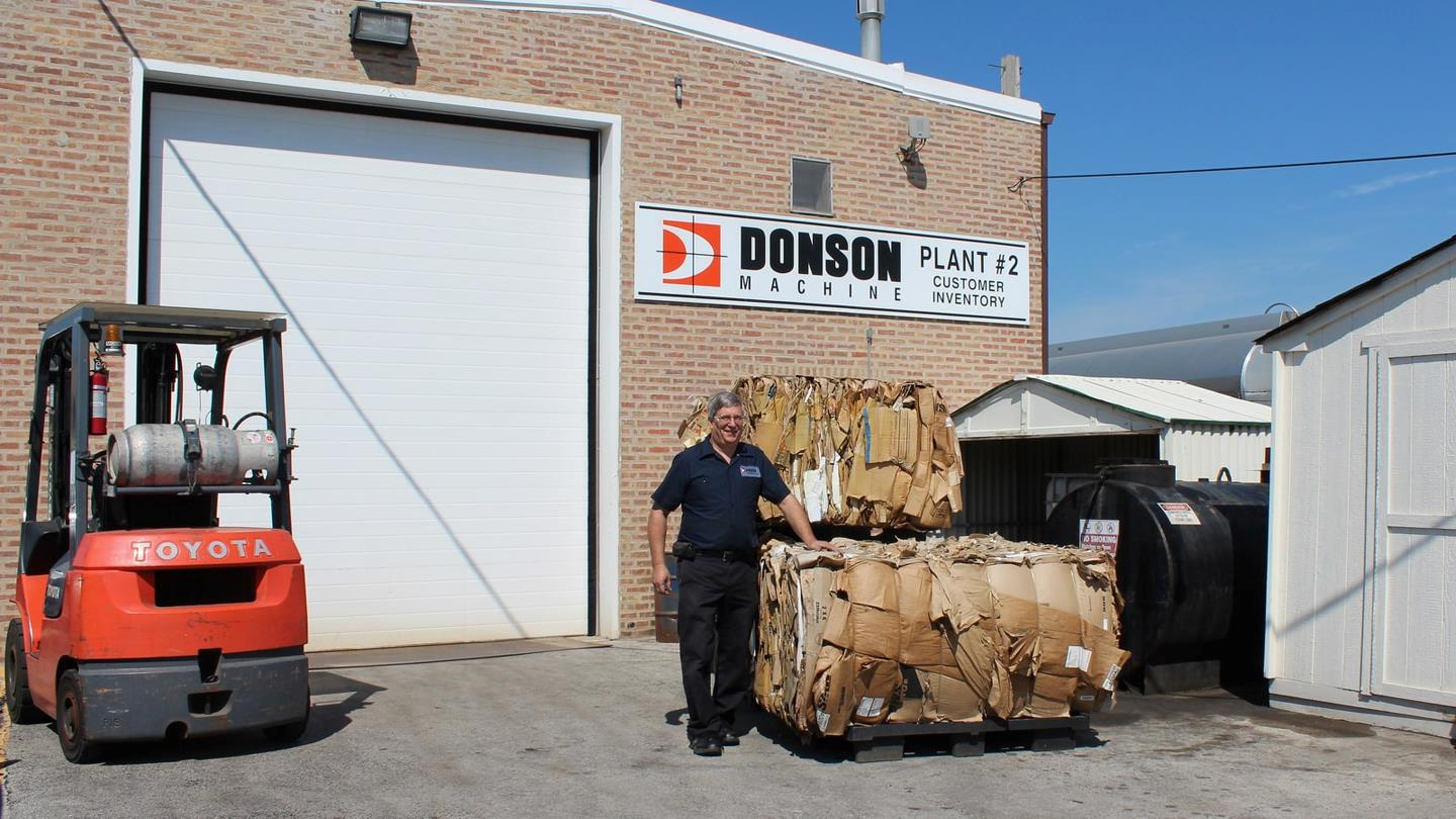 Compacted cardboard bales and fork lift truck at company Donson Machine