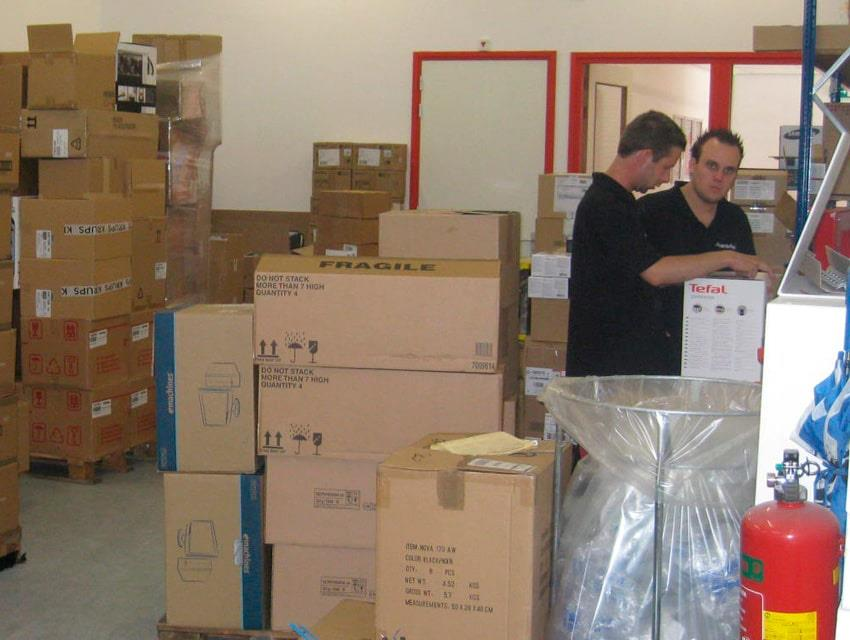 Cardboard boxes and two employees from Media Markt at storage room
