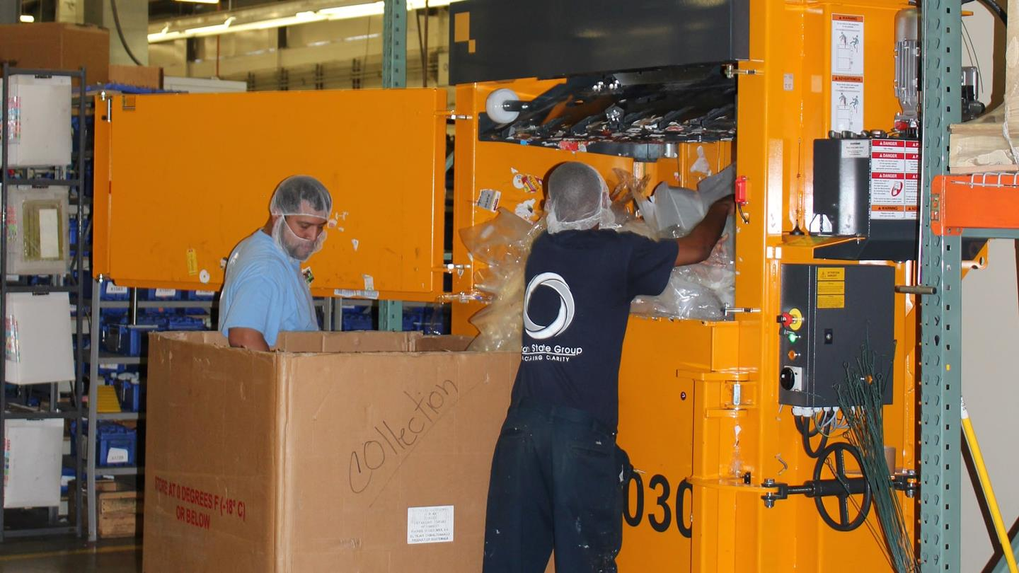 Two employees put plastic wrap into vertical baler from Bramidan