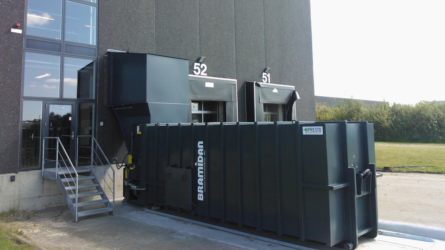 Bramidan compactor with filling through wall standing outside Prime Cargo building